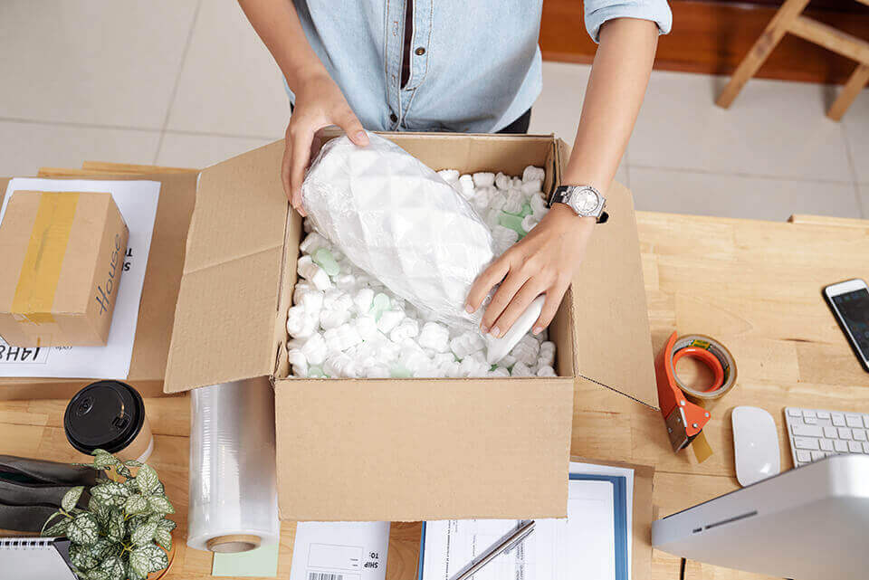 A woman packing a vase