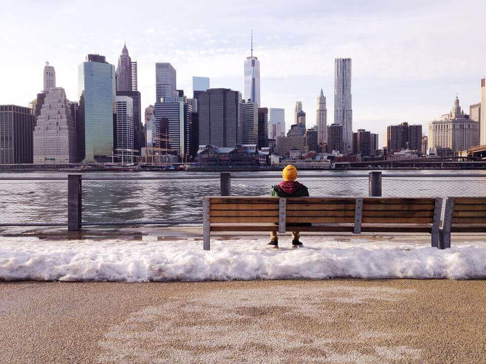 Man sitting on a bench and looking at the city skyline
