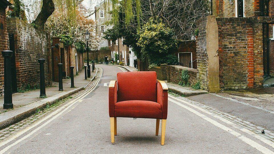 a red chair in the middle of a street