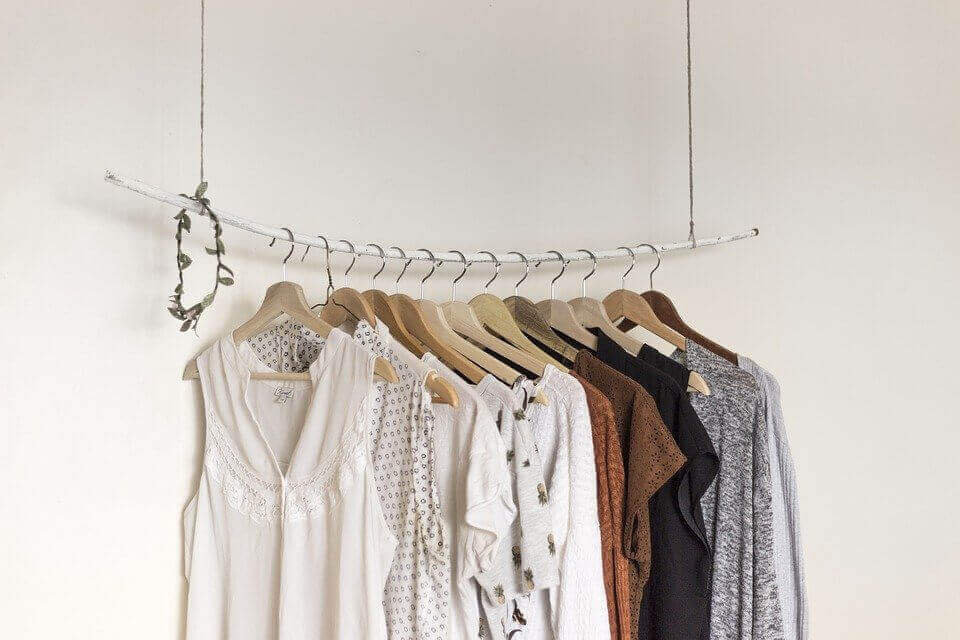 an image of a hanger with female apparel and a white wall