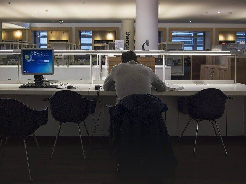 A man is sitting at a desk in a library.