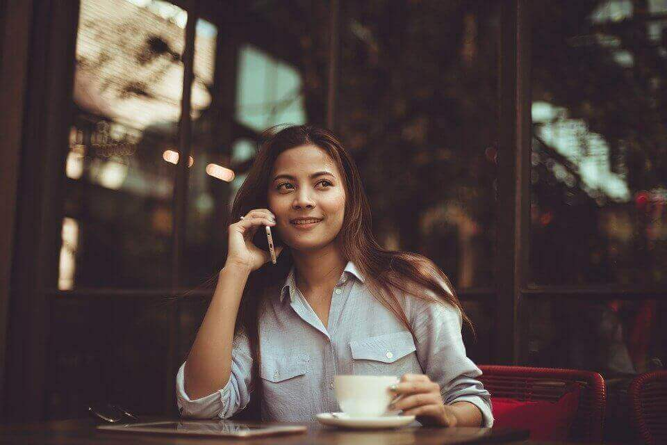 A girl talking on the phone in a cafe.