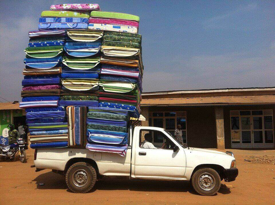 A truck with a stack of mattresses