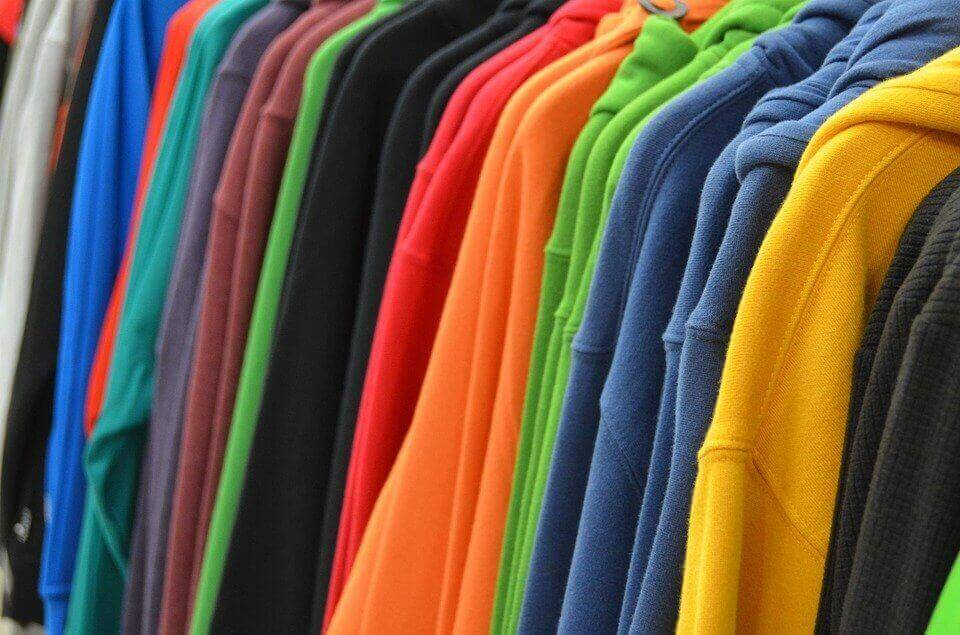 an image of colorful hoodies on hangers