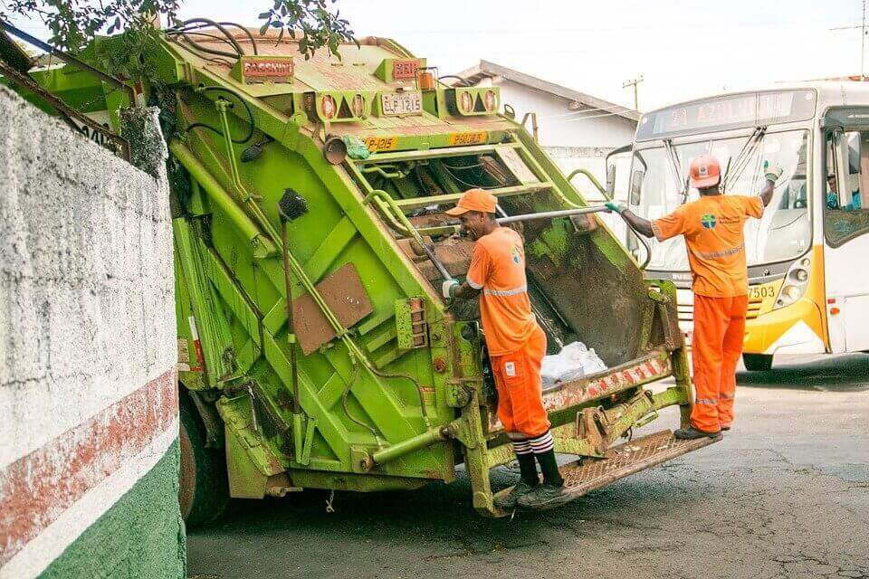 Trash collectors on a garbage truck