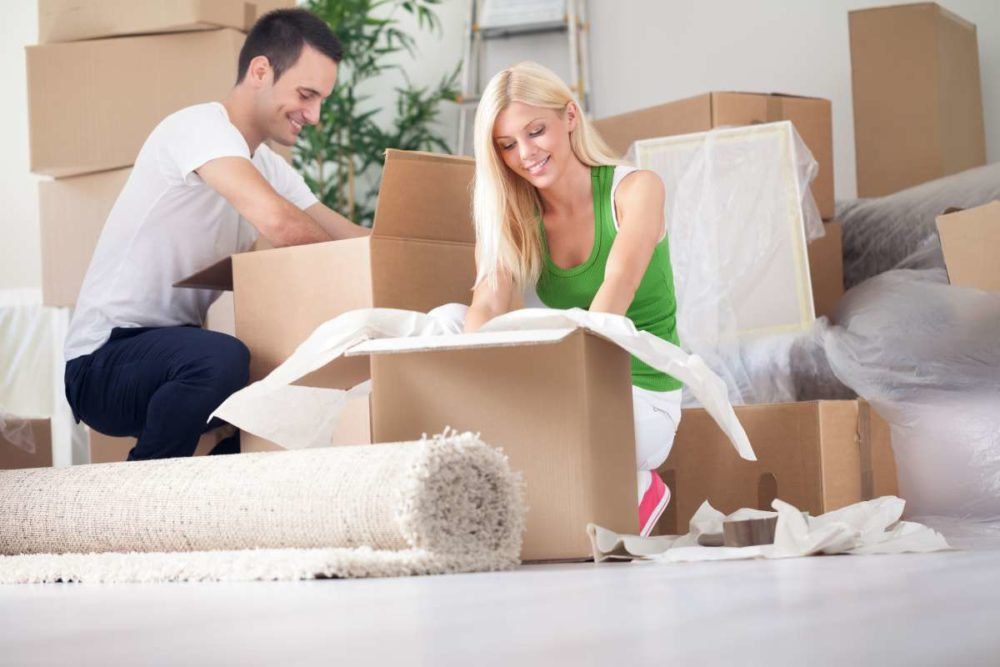 Smiling woman and man filling packages, a rolled carpet in front of them