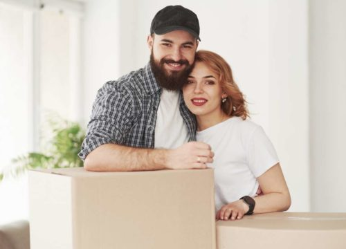 Couple with a cardboard box they got from New York movers