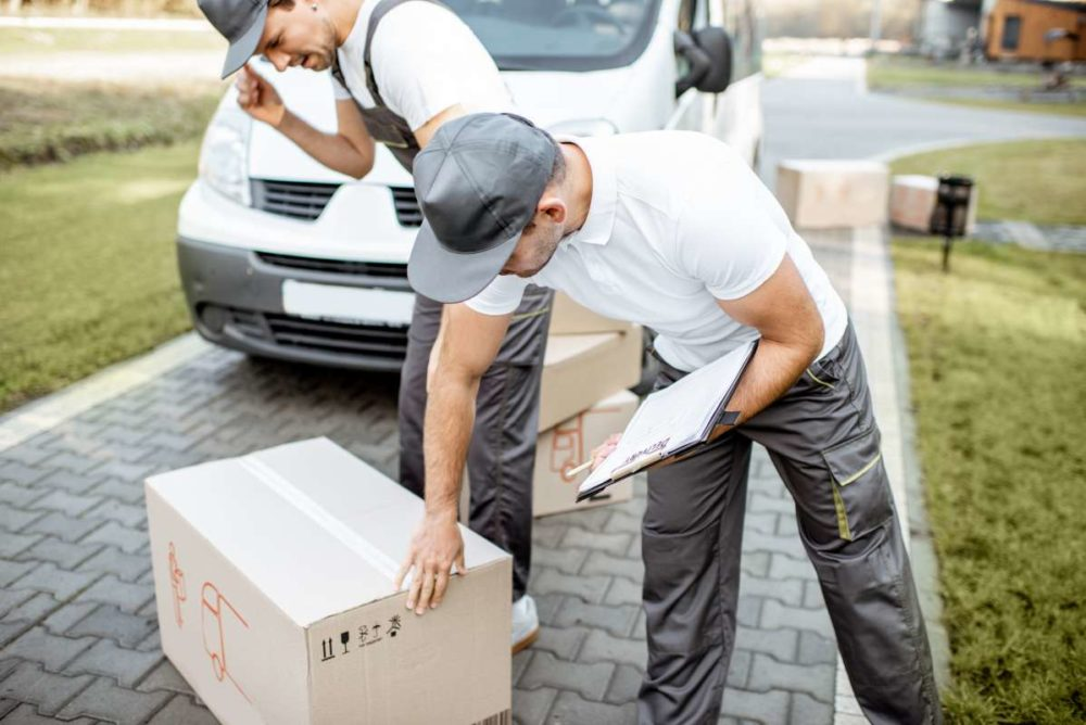 Two movers in New York inspecting a box
