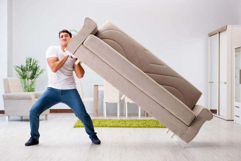 A man trying to lift a couch