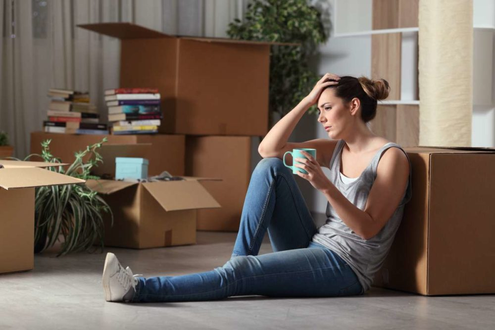Woman sitting on the floor, holding her head and a mug, surrounded by packages, waiting for New York movers